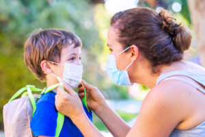 Parent and child with masks looking at each other get ready for first day of school
